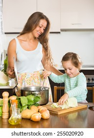 Happy women with little daughter cooking together at home kitchen