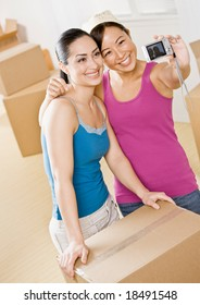 Happy women moving into new home and taking self-portrait near cardboard boxes
