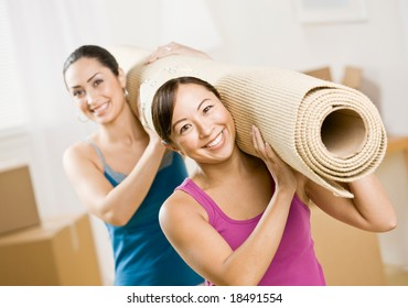 Happy women moving into new home and carrying rub