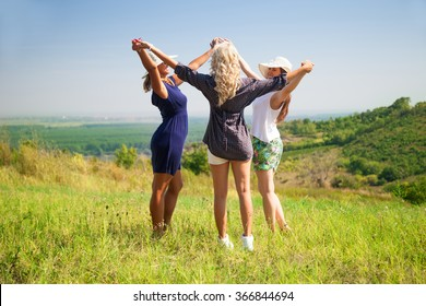 Happy women in nature holding hands and and having fun. Three girls enjoying in a meadow.