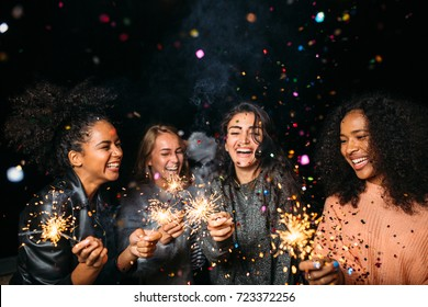 Happy women at night. Laughing friends with sparklers under confetti.