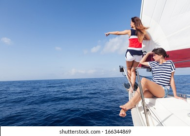 Happy women on the bow of a Sailboat pointing at something.Copy space