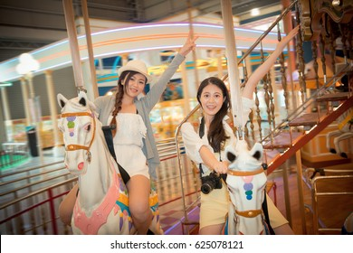 happy women riding carousel horses equipment in the popular amusement park and showing victor hands gestures to take pictures while travel together on abroad. vintage retro film color.