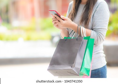 happy women shopping by mobile phone
