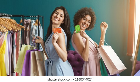 Happy women shopping. Two excited girls with credit cards and lots of bags