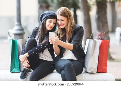 Happy Women with Smart Phone and Shopping Bags
