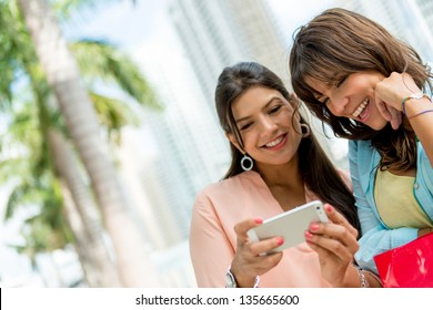 Happy women social networking from a mobile phone