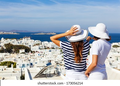 Happy  women standing  on the promenade and looking away, pointing at beautiful cityscape of Mykonos .Copy space