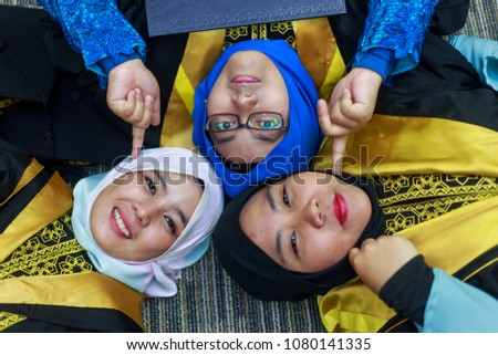 37174e73ee3 Happy women students in graduation dress lay down on floor. Friendship