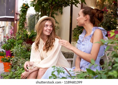 Happy women talking and laughing in a park with a green background.