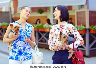 happy women talking on crowded city street, hold Yorkshire Terrier