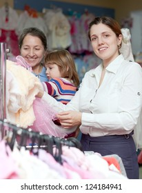 Happy women of three generations  chooses wear at children's clothes shop. Focus on woman