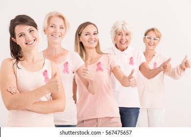 Happy women with thumbs up winning with breast cancer