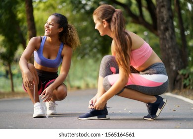 Happy women tying shoelace, Sporty fitness runner getting ready for workout at park. Running shoes, healthy lifestyle concept.