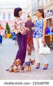happy women walking the dogs on city street