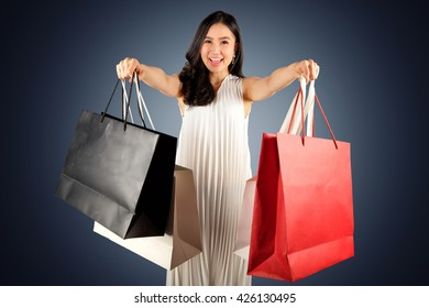 a happy women in white dress with shopping bag on dark blue background with clipping path