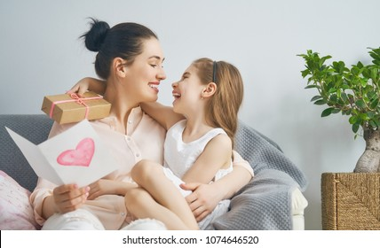 Happy women's day! Child daughter is congratulating mom and giving her postcard and gift. Mum and girl smiling and hugging. Family holiday and togetherness.