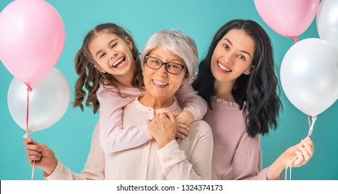 Happy women's day! Child daughter is congratulating mom and grandma giving them pink air balloons.Granny, mum and girl smiling and hugging on light blue background. Family holiday and togetherness.