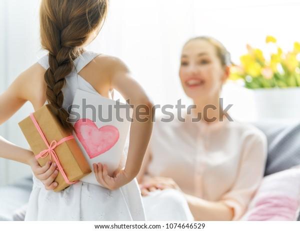 Fröhlicher Frauentag! Kindertochter gratuliert Mutter und gibt ihr Postkarte und Geschenk. Mama und Mädchen lächeln und umarmen. Familienurlaub und Zusammensein.