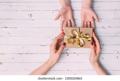 Happy women's day. Little child is congratulating mom and giving her gift on wooden background