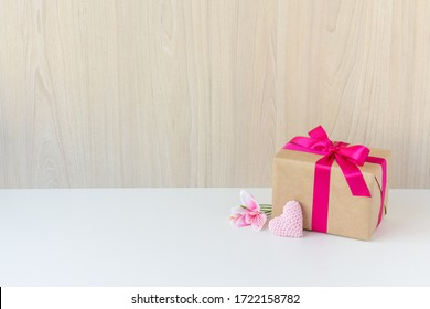 Happy Women's Day, Happy Mother's Day, Happy Valentine's Day and Happy Birthday. Have a flower, a crochet heart, a beautiful gift wrapped in a pink ribbon. Wooden background. White base. Copy space.
