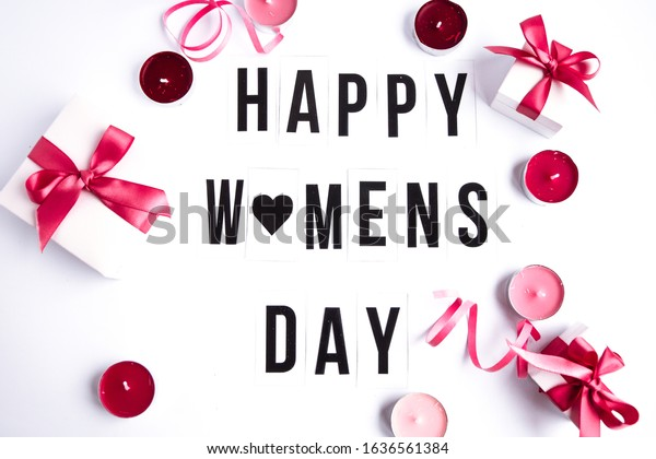 Happy womens day text on white table background, heart, holiday concept, greeting card, Present boxes with pink ribbon, candles