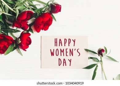 happy women's day text sign on craft card and beautiful red peonies on white wooden rustic background, flat lay. modern greeting card. womens day