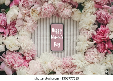 Happy Women's Day text sign on phone screen and peonies frame flat lay on rustic table cloth. Stylish floral greeting card. International womens day, girl power