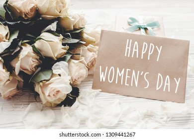 Happy Women's Day text sign on craft greeting card and white roses bouquet, gift box on wooden background. International womens day, 8 march. Floral greeting card