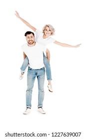 Happy wonderful couple having fun while man piggybacking blonde woman isolated on white