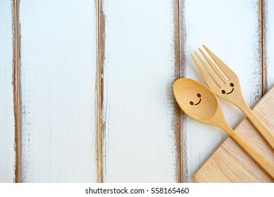 Happy wooden fork and spoon with cutting board on wooden texture of dining table. Concept about love and relationship with copy space.