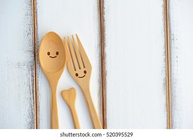 Happy wooden fork and spoon with love on wooden texture of dining table. Concept about love and relationship.