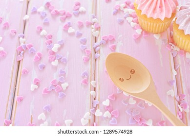 Happy wooden spoon with sweet mini hearts candy on pink wooden background. Homemade cupcake preparation.Concept about love and relationship.Valentines day in soft style.Together and happiness idea.
