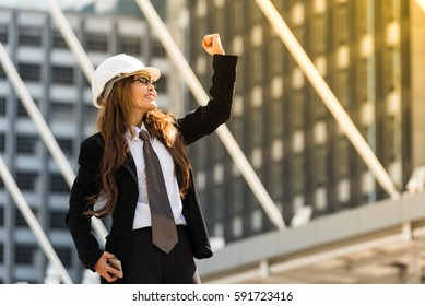 Happy in work can win a game like  a boss. Business woman holds up fist in the air out side the office . After she and her worker work  hard everyday. She very happy because her job finished on time.