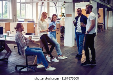 Happy to work together. Group of young business people communicating while working in the office