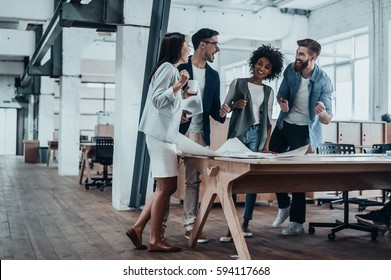 Happy to work together. Group of young business people talking and smiling while standing near the wooden desk in the office