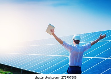 Happy working solar station raising his hands with tablet computer on a background of photovoltaic panels. Science solar energy.