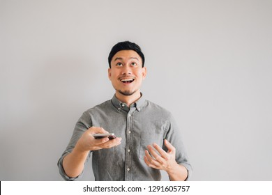 Happy and wow face of Asian man use smartphone.