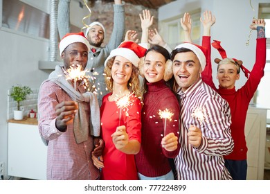 Happy xmas guys and girls holding bengal lights while enjoying home party