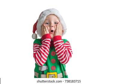 Happy Xmas and New Year holiday! Shocked and surprised kid with red Christmas hat with head in hands. Cheerful smiling little boy opens his mouth in surprise.