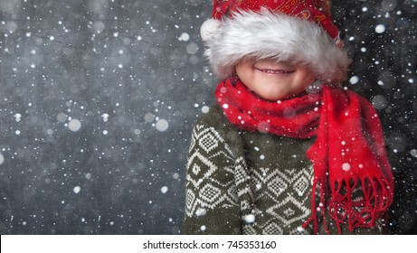 Happy xmas and New Year. Portrait of child in Santa red hat waiting for Christmas gifts. Smiling funny kid at Christmas night. Kid closed eyes with hat in anticipation of miracle.