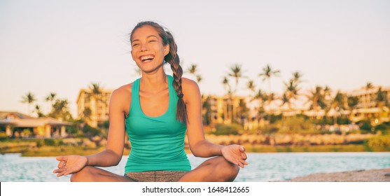Happy yoga Asian girl having fun meditating on outdoor summer beach travel vacation Caribbean resort healthy active lifestyle. Zen meditation woman laughing panoramic header banner.