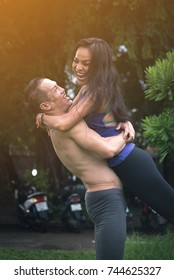 Happy yoga couple hugging and laughing with full love after not having met so long at outdoor.