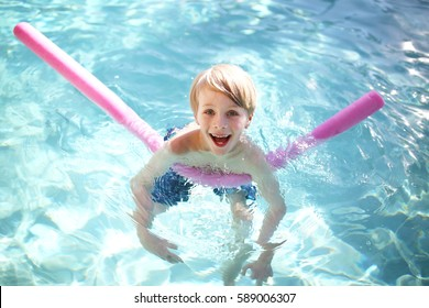 A happy, young, 7 year old boy child is smiling as he takes swimming lessons with a floating fun noodle outside in the pool on a summer day.