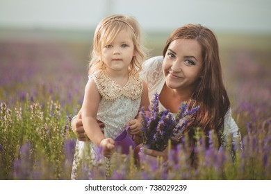 Happy young adorable brunette mother mom posing kissing her tiny little daughter child girl in lavender field meadow with bouquet maund trug of purple flowers.