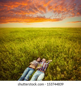 happy young adult couple lying on the grass over sunset