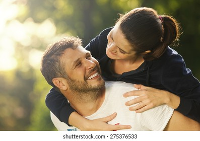 Happy young adult couple outdoors smiling, she holding on his back