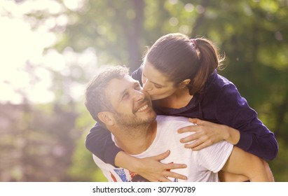 Happy young adult couple outdoors kissing and smiling, she holding on his back