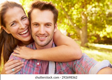 Happy young adult couple relaxing in the countryside, portrait