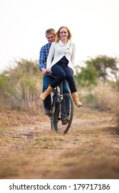 Happy young adult couple riding old bicycle on dirt road